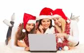 Three beautiful girls on the New Year's Eve looking at laptop — Zdjęcie stockowe