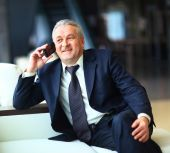 Smiling businessman sitting and talking on the phone at office — Stock Photo