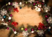 Green fir branches on the wooden floor with darkening at the edges with Christmas decorations — Stock Photo