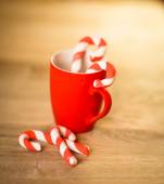 Mug Of Tea Or Coffee. Sweets. Christmas Decorations. Red Balls And Bells. Wooden Background. — Stock Photo