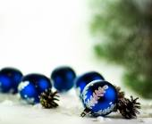 Blue Christmas balls on white background with fir cones — Stock Photo