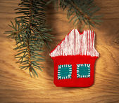 Beautiful Christmas house with fir paws on wooden background — Stockfoto