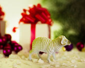 Toy lamb with Christmas balls and fir paws gifts — Stock Photo