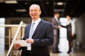 счастливый зрелой деловой человек, глядя на камеру с удовлетворением в офисе — Стоковое фото