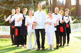 Large group of waiters and waitresses standing in row. — Stock Photo