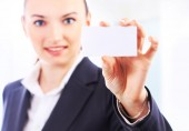 Beautiful businesswoman with the business card in the office — Stock Photo