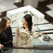 Business people on escalator, two young businesswomen talking — Stock Photo #69024613