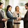 Group of business people congratulating their handshaking colleagues after signing contract — Stock Photo #69024655