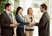 Group of business people congratulating their handshaking colleagues after signing contract — Stock Photo