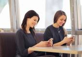 Two girls are in correspondence to the phone in cafe — Stock Photo