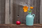 Marigold flowers in small vase and red apple — Stock Photo