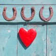 Three old rusty horseshoe luck symbol and red heart on door — Stock Photo #57629491