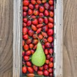 Rose hips fruit and pear in old window frame — Stock Photo #58406631