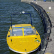 Yellow motor boat near sea dock and lighthouse — Stock Photo #58406681