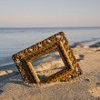Vintage golden picture frame on sea resort beach — Stock Photo #58990901
