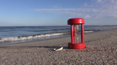Ancient red broken hourglass sandglass on sea beach sand. Summer time concept — Stock Video