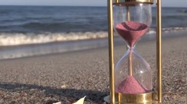 Red sand motion in ancient sandglass hourglass on beach sand — Vídeo de stock