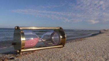 Ancient brass sandglass hourglass on sea beach — Stock Video