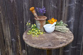 Mortars on old table and various medical herbal medicine flowers — Foto Stock