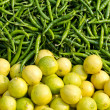 Fresh green chili peppers and lemons in asian market — Stock Photo #61478783