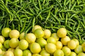 Fresh green chili peppers and lemons in asian market — Stock Photo