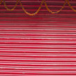 Red painted corrugated metal door and flowers garland — Stock Photo #63185803