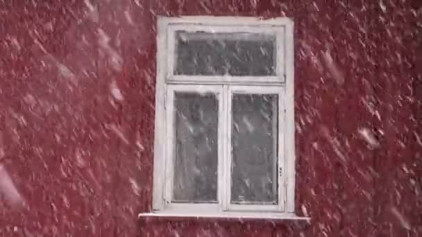 Snowfall and window in wooden village house — Vidéo