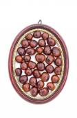 Conker fruits seeds in wooden picture oval frame isolated — Stock Photo