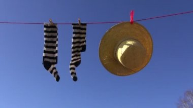 Laundry line with woman socks and summer straw hat in wind on sky background — Stock Video