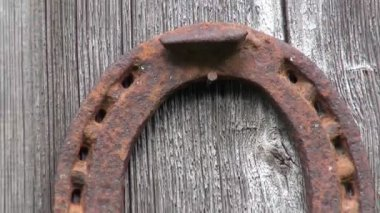 Vieux rouillé fer à cheval accroché sur le mur en bois ancien — Vidéo