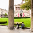 Berlin - Germany  - September 28, 2014. Couple of tourists sit on the wall among the columns and watch at Old National Gallery in Berlin, Germany. The building of this gallery was biult  in 1876 — Stock Photo #63322193