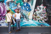 Berlin - Germany  - September 29, 2014. Tourists look at mural paintings at East Side Gallery - over 1 km long mural gallery painted on oryginal part of Berlin Wall — Stock Photo