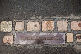 Berlin, Germany - Brass plaque embedded in the asphalt  showing at which point there was the Berlin Wall. — Stock Photo