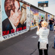 Berlin - Germany - September 29. People walks, and make pictures, along the Berlin Wall in East Side Gallery - over 1 km long part of historical Berlin Wall. September 29, 2014 in Berlin, Germany — Stock Photo #63583667