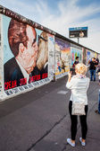 Berlin - Germany - September 29. People walks, and make pictures, along the Berlin Wall in East Side Gallery - over 1 km long part of historical Berlin Wall. September 29, 2014 in Berlin, Germany — Stock Photo