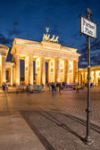 Berlin - Germany - September 29 People walk on Pariser Platz. Quadriga located on top of Brandenburg Gate in Berlin, Bermany. Night picture of Quadriga with dark, black sky. — Foto Stock