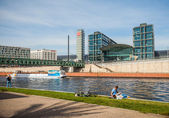 Berlin - Germany - September 28.  People rest on the banks of river spree. On the background main railway station in Berlin (Hauptbahnhof). Berlin - Germany - — Stock Photo