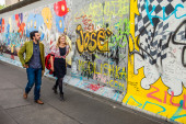 Berlin - Germany - September 29. Tourists walk along the outside gallery - West Side Gallery - over 1km of Berlin Wall with colorful murals. Berlin - Germany - September 29, 2014 — Stock Photo