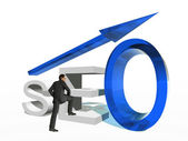 Businessman standing over a seo symbol — Stock Photo