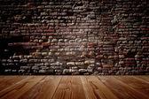 Dřevěné staré podlahy a cihlová zeď — Stock fotografie