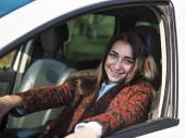 Young pretty smiling girl sitting behind the wheel of a car — Stock Photo