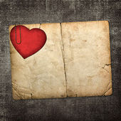 Old paperboard card with red paper heart on a dark fabric backgr — Stock Photo
