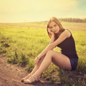 Young sensual smiling blond woman sitting on the grass outdoors — Stock Photo