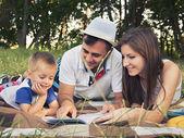 Parents ayant un enfant lisant un livre à l'extérieur — Photo