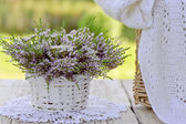 Bouquet of flowers in basket and scarf — Stock Photo