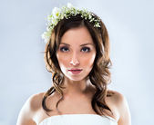 Beautiful bride wearing white wedding dress with flowers on her head — Stock Photo