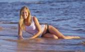 Young girl on a white T-shirt sitting in the water at the beach — Stock Photo