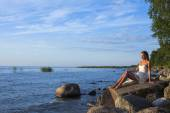Young girl in white dress sitting on the rocks on the shore of lake — Stock Photo