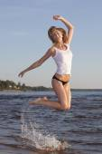 Young girl on a white T-shirt standing in water at the beach — Stock Photo