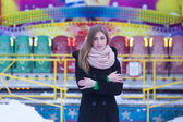 Girl in black coat on the background of the carousel — Fotografia Stock